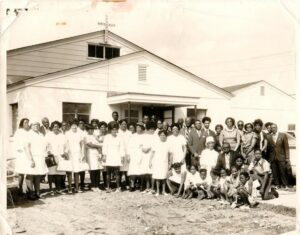 Group of Black people in front of building in Sunday best.