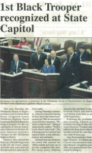 Newspaper clipping about recognition of Black trooper, Ronnie Johnson, with picture of group at Oklahoma state capitol podium.